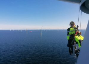 female wind turbine technician hanging from the ropes over the ocean